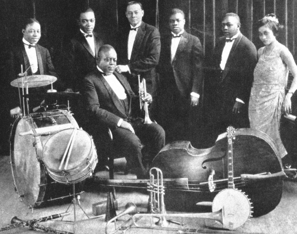 3 1923년 킹 올리버가 이끄는 크레올 재즈밴드에 몸담고 있던 젊은 시절의 루이 암스트롱. 트럼펫을 손에 들고 앉아있는 사람이 킹 올리버이며 루이 암스트롱은 위 왼쪽에서 네번째에 위치해있다. 가장 오른쪽에 위치한 여성이 그의 두 번째 부인인 릴리 하딘..jpg